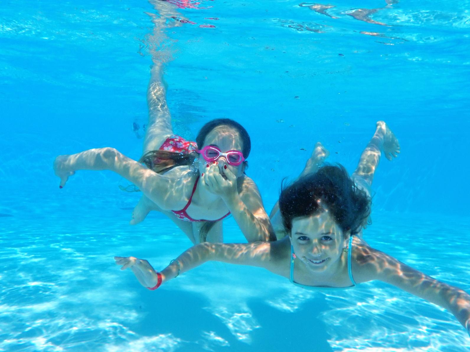 Enfant nage sous l'eau dans une piscine